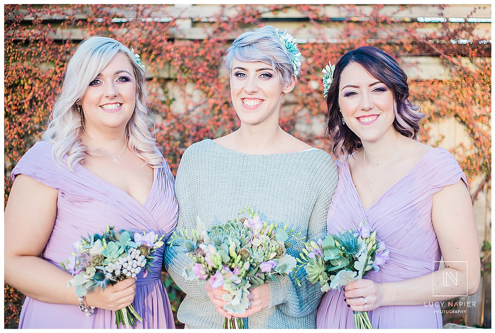 The bride and her bridesmaids pose with their bouquets