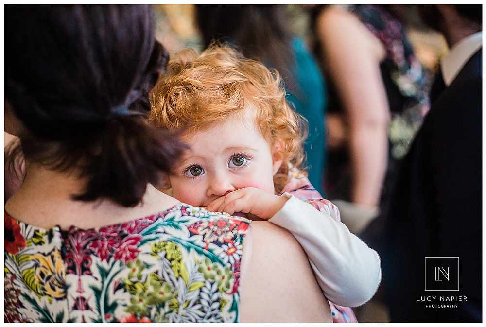 Little girl with big brown eyes peeps over her mums shoulder
