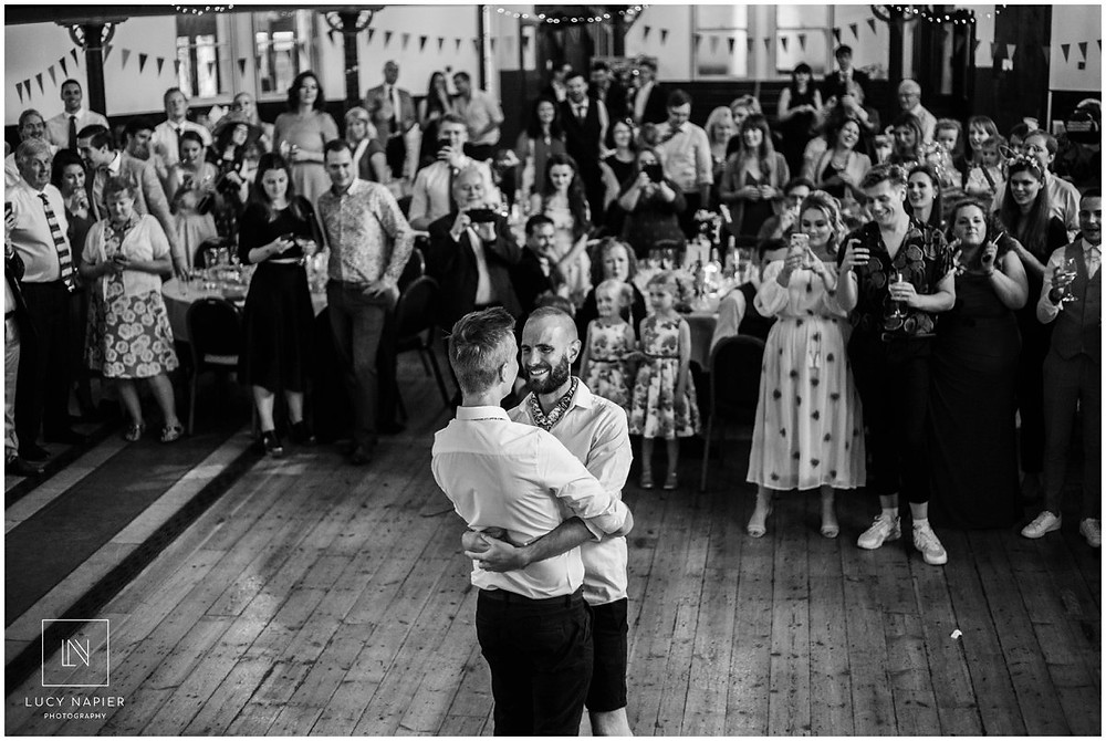 two grooms embrace in their first dance in London wedding venue the round chapel
