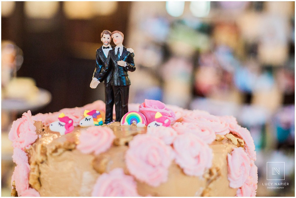 two grooms on the top of a unicorn wedding cake