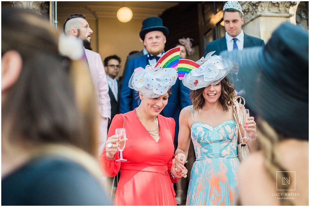 two guests with rainbow hats sip champagne