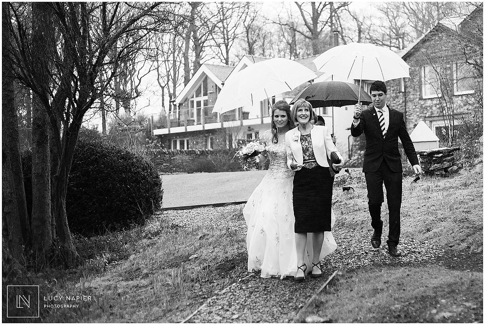 white umbrellas as the bride makes her way to the Lake house