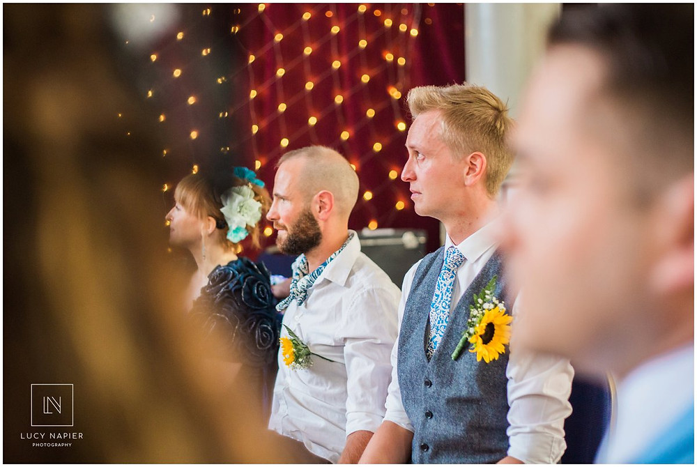 grooms cry at an emotional performance at their wedding