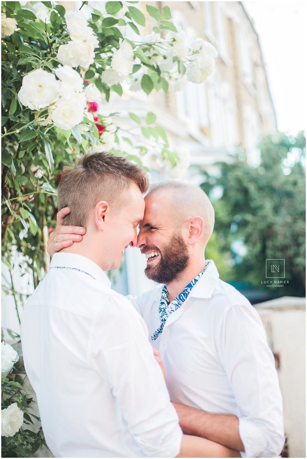 groom portraits two grooms embrace surrounded by flowers