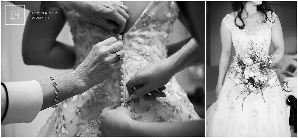 The bride gets into her wedding dress helped by her mum and sister