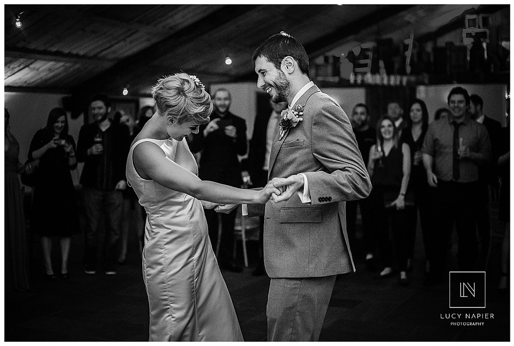 The Bride and Grooms first dance, their guests look on, image in black and white