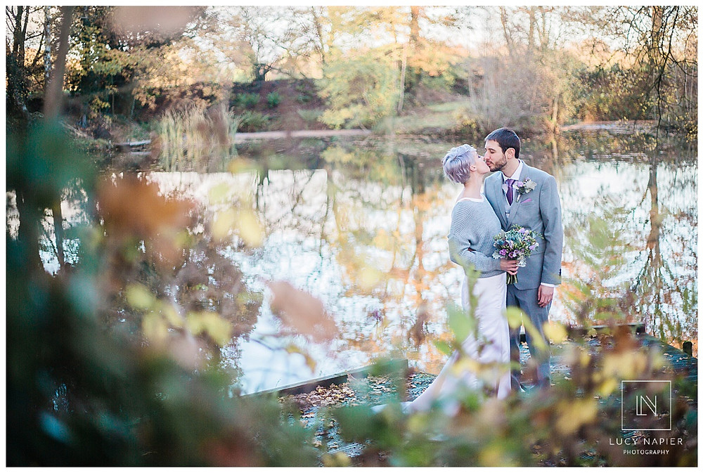newly wed couple kiss in front of a beautiful lake
