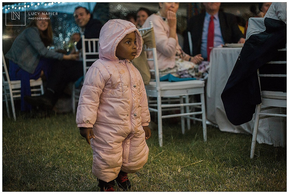 child in a snowsuit at a wedding