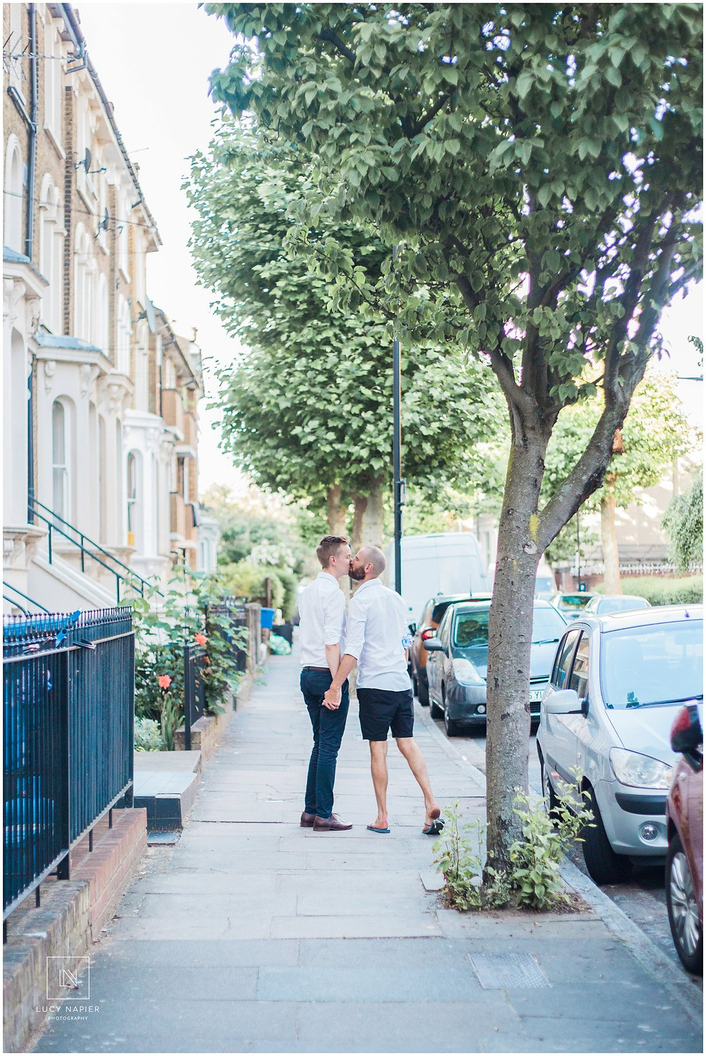 two men walk down a street in London holding hands and kissing