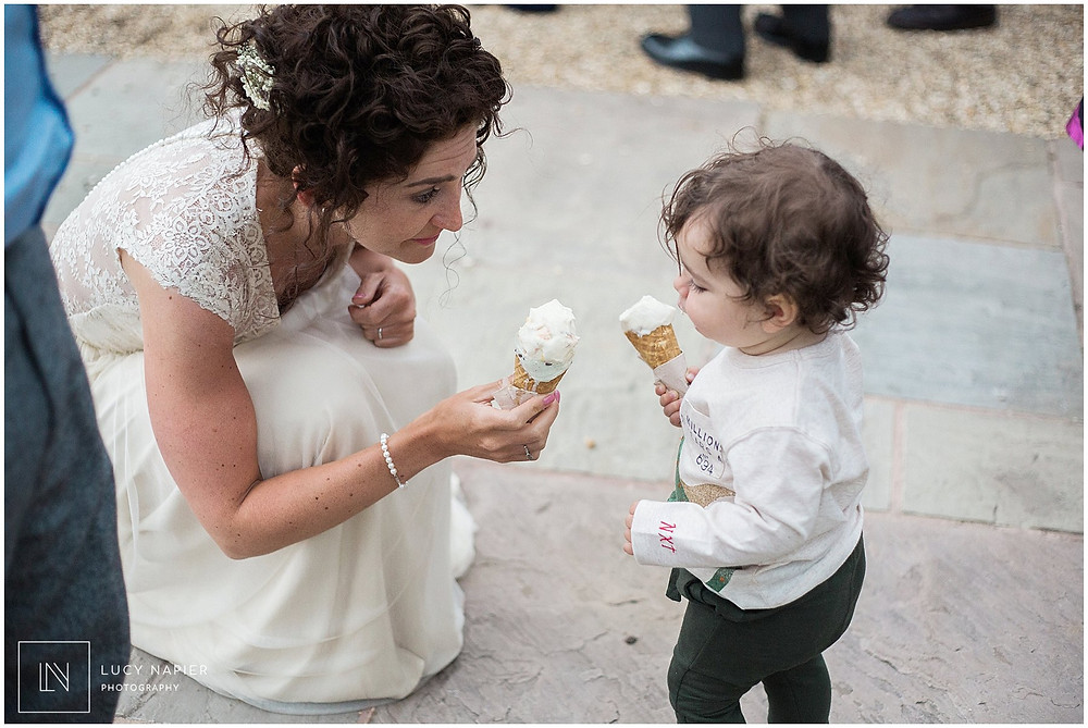 Bride and little boy eat ice-cream