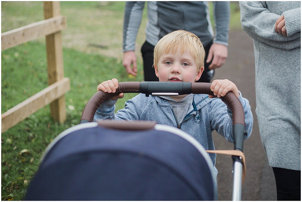 big brother pushes his sister in the pram