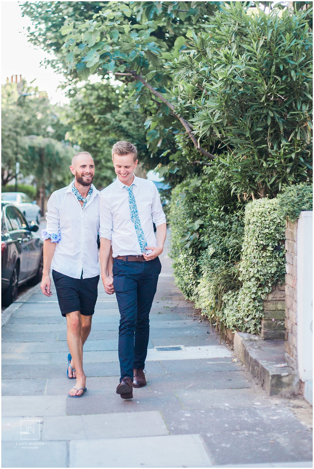 two grooms walk down the street holding hands at a same sex wedding at the round chapel London