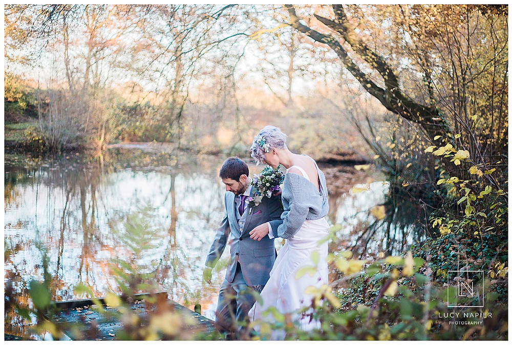 the bride and groom head down to the lake for some pictures alone together, autumn colours surround them