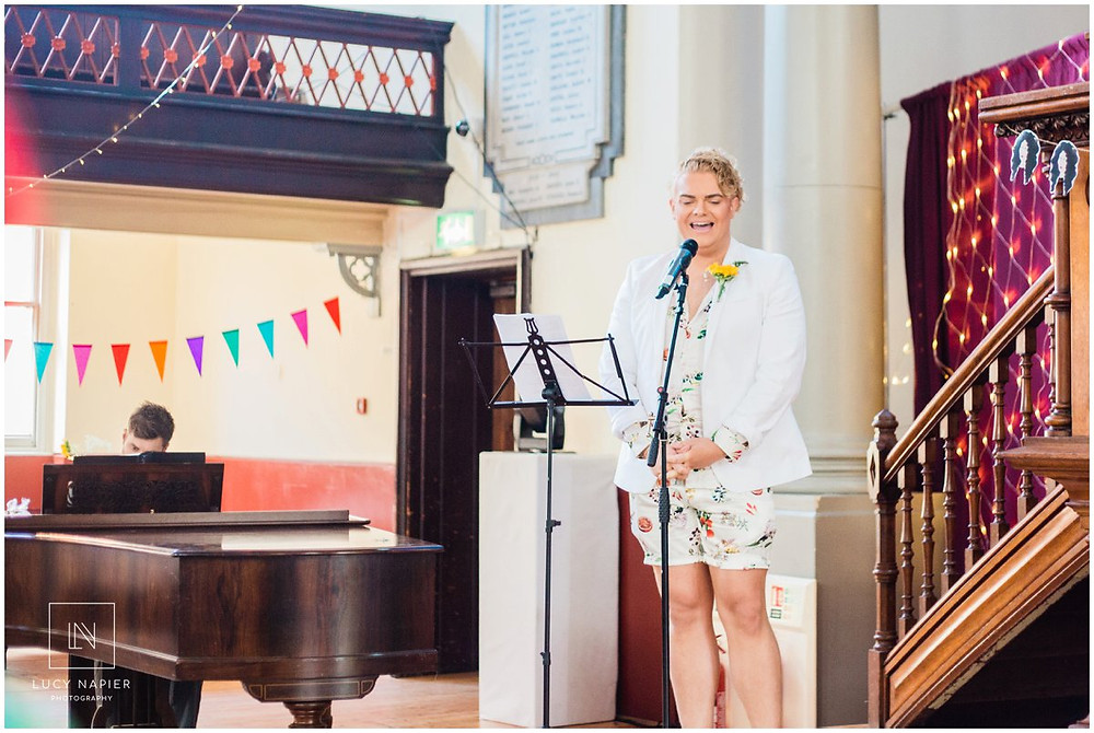 a performer singing at a wedding in the round chapel London