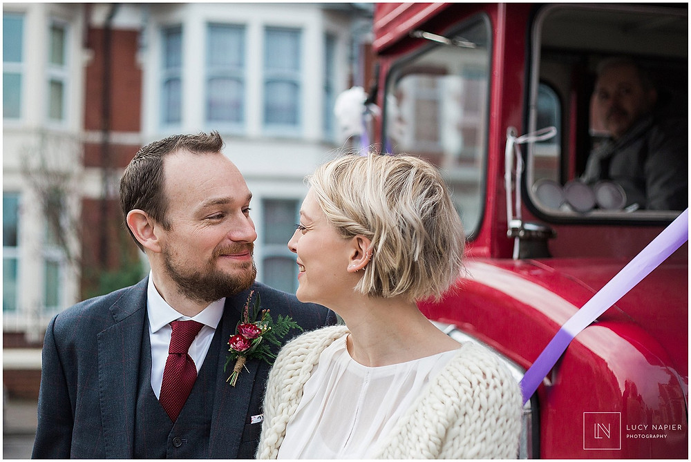 the bride and groom pose in front of a london bus