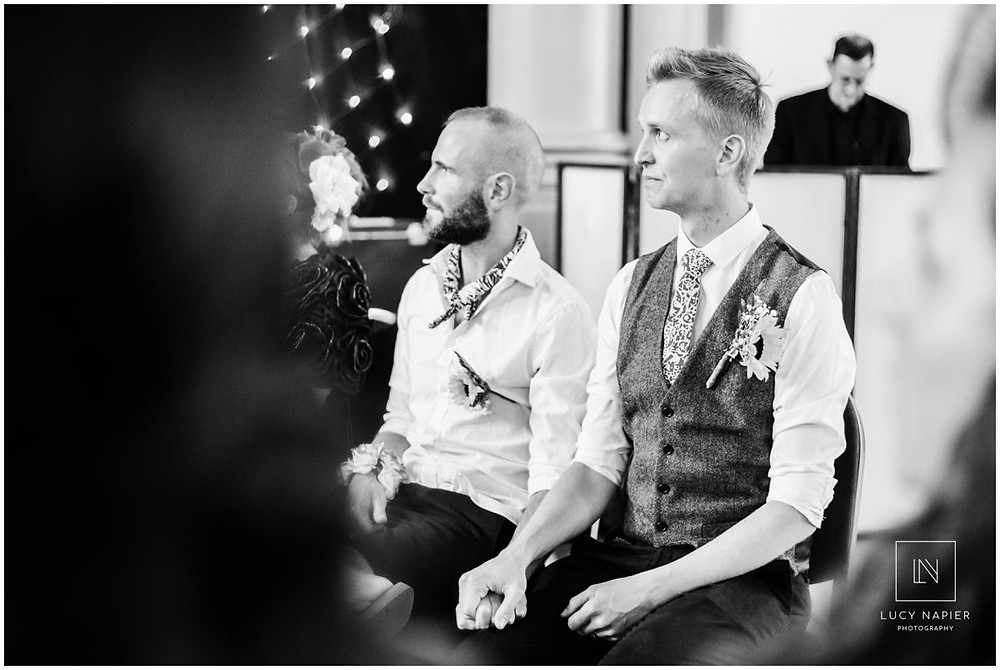 groom cries whilst watching an emotional performance at his wedding