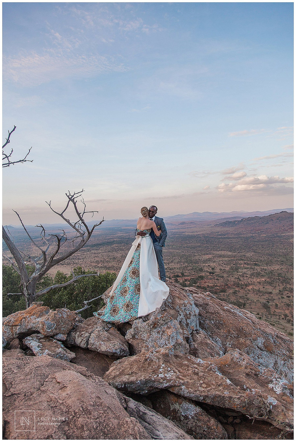 bride and groom pose on a hill african dress draped