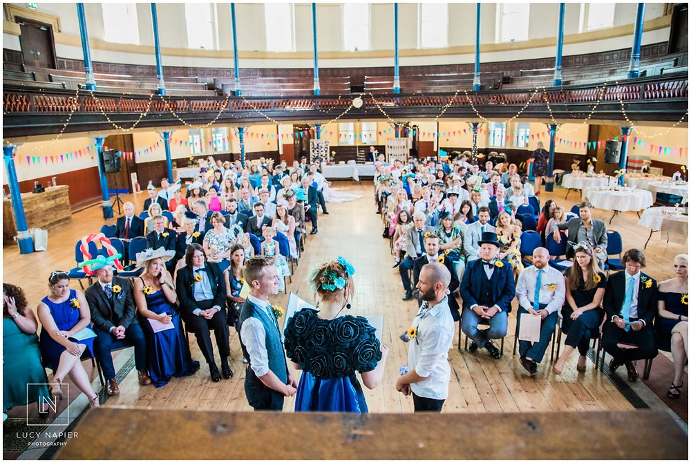 a crowd watch as two grooms marry in the round chapel east London