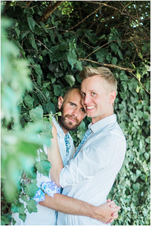 two grooms embrace in a leafy green street in London