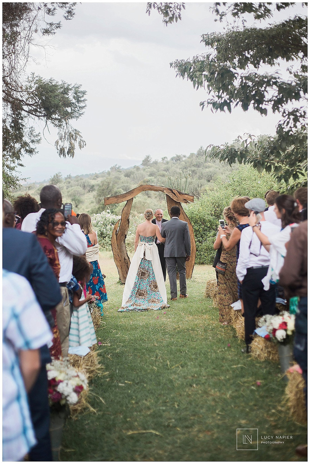 The bride and groom stand under an arch
