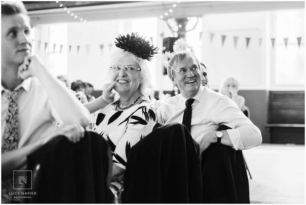 parents of the the groom smile at speeches