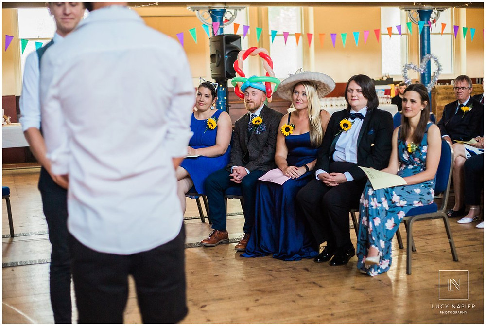 guests watch as two grooms say their vows