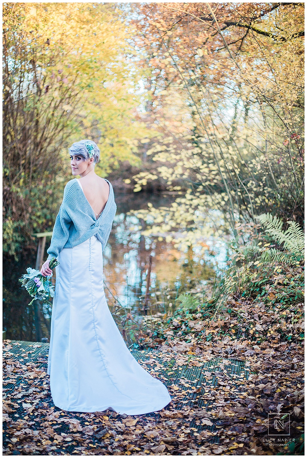 the bride stands alone on the edge of the lake with her bouquet