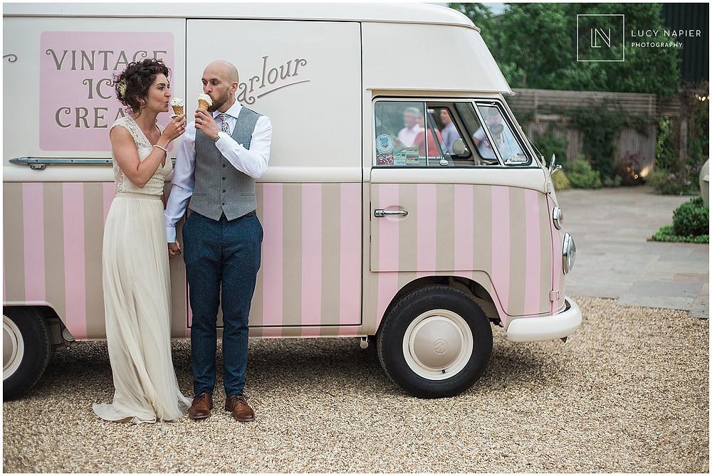 bride and groom eat ice-cream from a vintage camper van