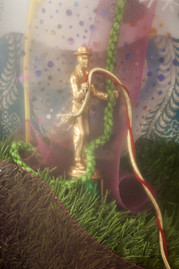 """Detail. Vintage trophies, fabric, chord, fake grass, metal, plastic in shadowbox with Fresnel lens, 29"""" x 29"""" x 3 1/2""""."""