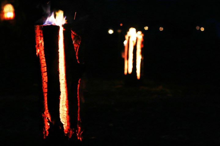 The log candles burning on the way into the Barn Garden