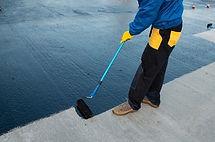 waterproofing-coating-worker-applies-bit