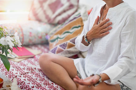 Self-Healing Heart Chakra Meditation. Woman sitting in a lotus position with right hand on