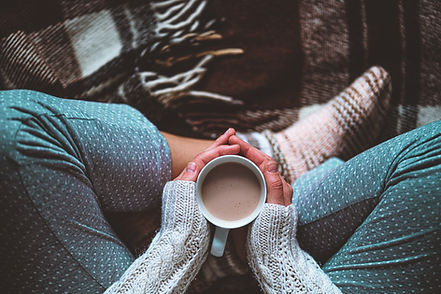 Kopie von Cozy woman in knitted winter warm socks and in pajamas holding a cup of hot coco