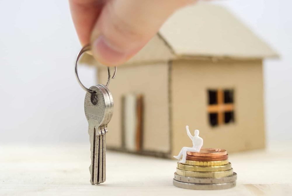 Mão a segurar numa chave de casa ao lado de uma pilha de moedas e uma miniatura de uma casa atrás