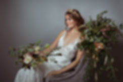 bride sitting on floral chair throne with bridal bouquet