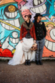 Hipster bride and groom holding wedding bouquet in front of graffiti wall Shoreditch London