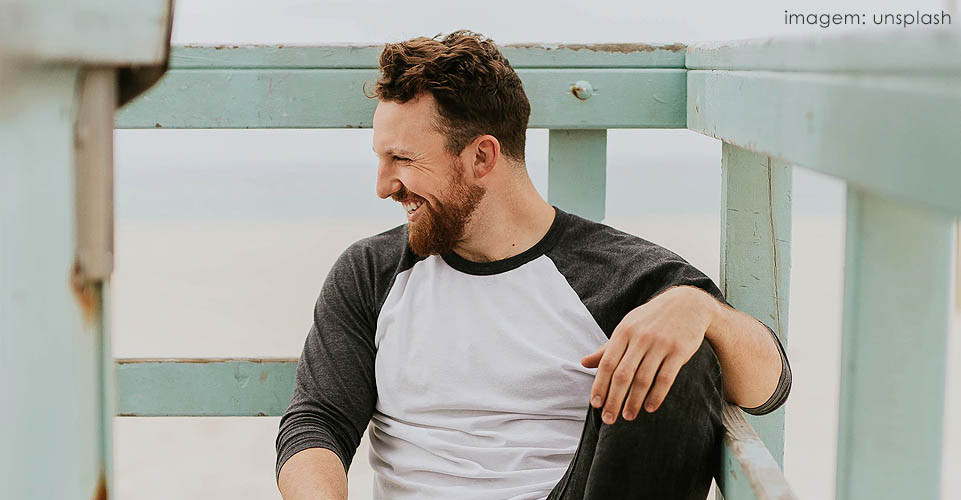 Homem com barba sorrindo e olhando para o lado