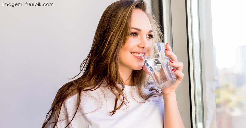 Mulher de cabelos longos, sorrindo e bebendo um copo com água