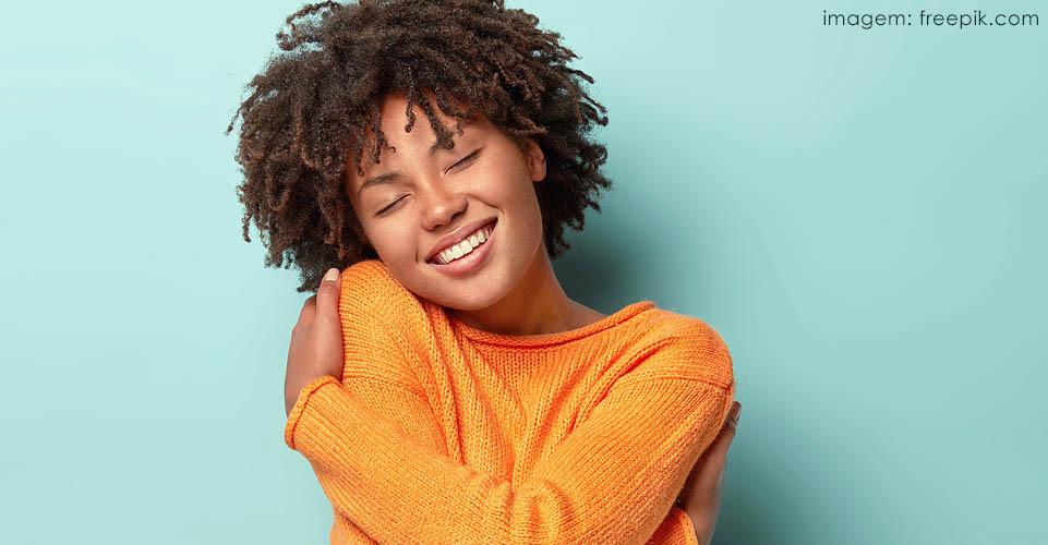 Mulher negra de blusa laranja com cabelo afro sorrindo e se abraçando