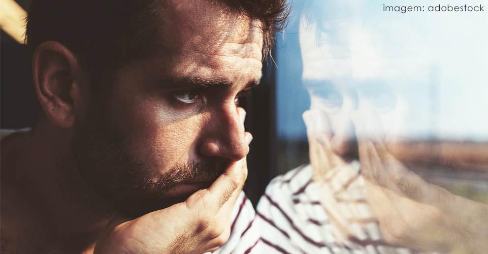 Homem de barba preocupado com a mão no rosto