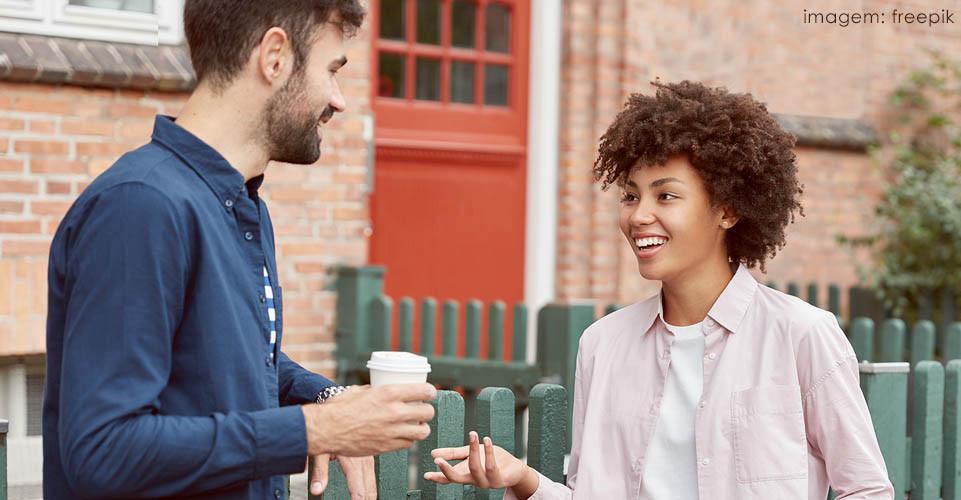 Mulher negra de cabelo afro sorrindo e conversando com homem de barba segurando um copo de café
