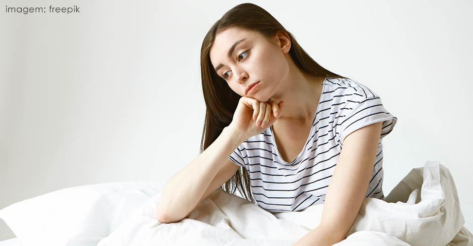 Mulher branca de cabelos longos sentada em sua cama com mão no queixo e expressão preocupada