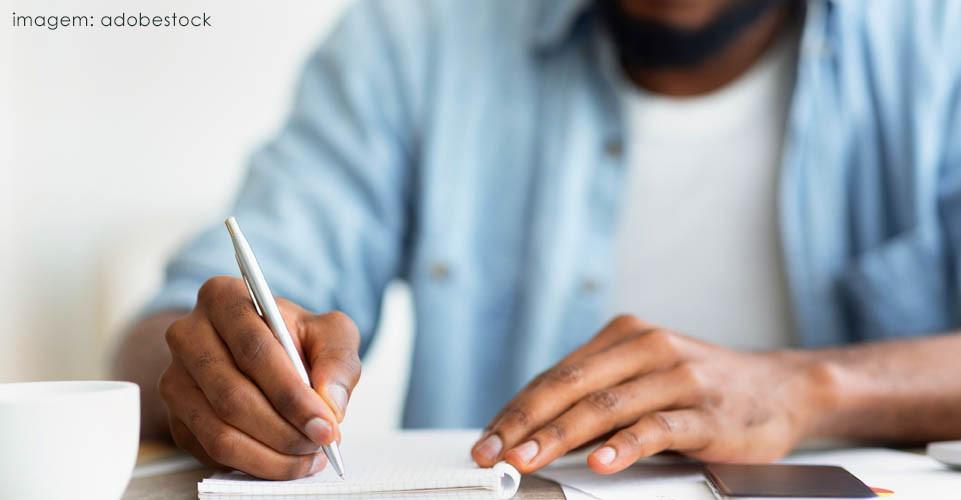 Homem negro escrevendo em um caderno sentado à mesa