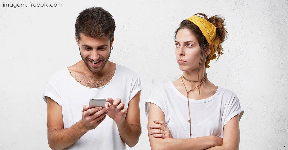 Homem olhando celular e mulher com ciúme
