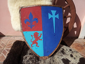 Escudo feito para ser usado nos treinos de esgrima histórica e combate medieval. Foi pintado com o brasão de seu dono, possui borda coberta por couro bovino e tem três posições diferentes de pegas.