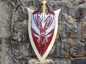 Escudo inspirado no Crimson Glory Shield, do MMORGP Mu online. Foi feto com duas camadas de compensado 4mm e foi pintado direto na madeira. Possui desbaste nas laterais e detalhes em madeira e em couro para simular todos os detalhes da peça que serviu como referência.