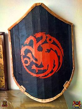 Escudo feito com tábuas de Pinus. Tem borda revestida por soleta bovina e a face externa foi revestida com couro sintético. Foi pintado com o brasão da Casa Targaryen, do universo de As Crônicas de Gelo e Fogo ( Game of Thrones).