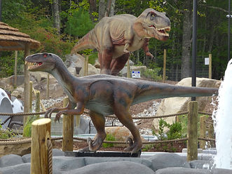 A raptor and a T-Rex dinosaurs on the Raptor Falls mini golf course