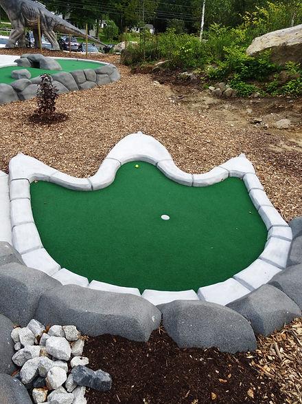Raptor falls mini golf course dinosaur footprint hole in one.
