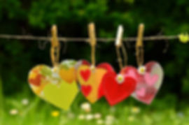 hearts-in-a-row-in-sun-WR.jpg  Four vibrant fabric heart shapes hanging from  washing line in a sunny garden.